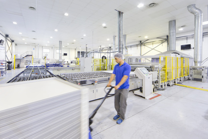 Worker pulling pallet of solar panels on factory floor